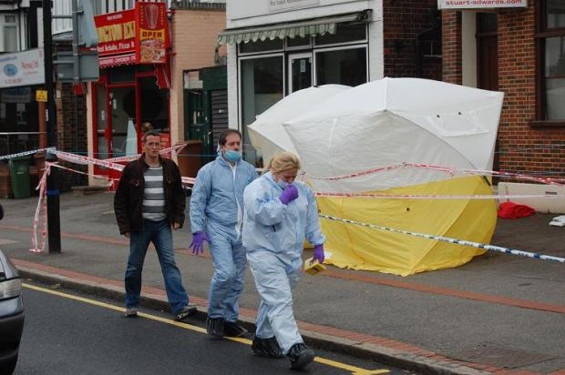 Forensic officers walk past police tents erected at the scene