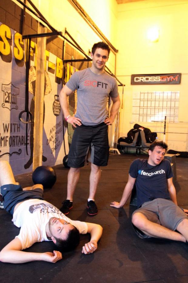 Shattered: Graham Moody, left, and Danny Butterwick, right, collapse after competing Tom Bold's, centre, crossfit workout