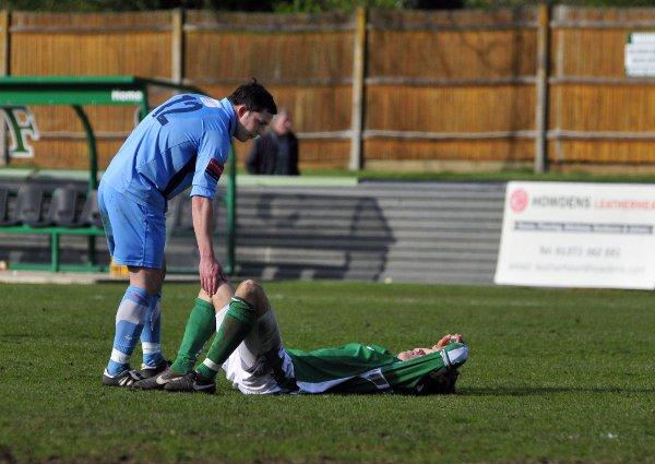 Down and out: Kingstonian's Bobby Traynor consoles Harry Ottaway after relegation