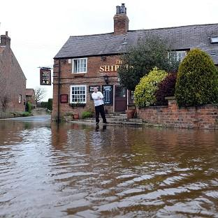 Richard Taylor looks at floodwater from the River Ouse as it rises to the steps of the Ship Inn at Acaster Malbis near York
