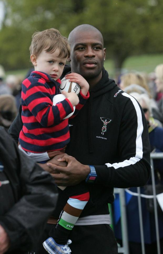 Waiting game: Winger Ugo Monye with a young Quins fan waiting to see the Queen at Roehampton Gate on Tuesday
