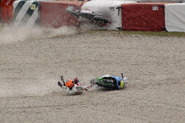 Big impact: While his bike crashes into the tire wall, Gino Rea tumbles through the gravel with Julian Simon's bike after the pair collided on Saturday. Picture: Graham Holt