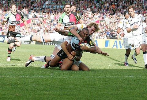 Muscle: Quins centre Jordan Turner-Hall dives over for his first half try despite close attention from the Sale defence