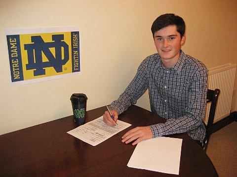 On his way: Liam Cox signs his scholarship at the University of Notre Dame in Indiana