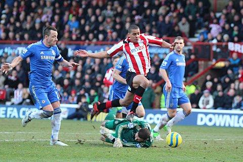 Penalty: Brentford's Tom Adeyemi is felled by Chelsea goalkeeper Ross Turnbull in Sunday's 2-2 draw at Griffin Park