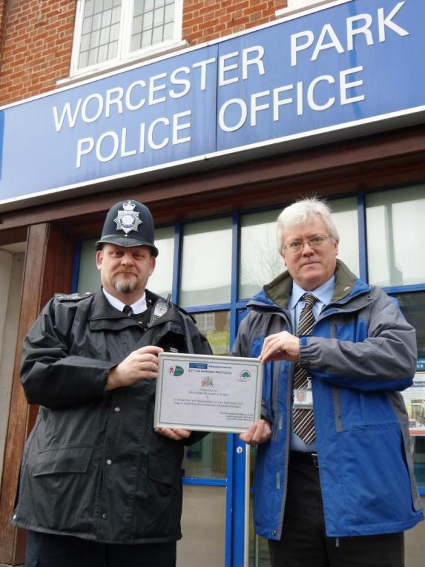 Sgt Ashley Bennetts with Brian Cox of Sutton's Trading Standards with a 'Banking Protocol' certificate outside Worcester Park Police Office