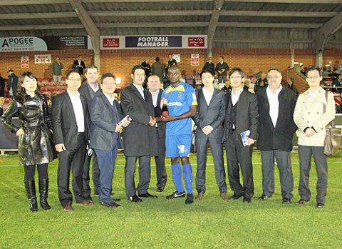 Noodle time: Representatives of Nongshim present Will Antwi with his man of the match award after the Torquay match in September - the night Terry Brown was sacked