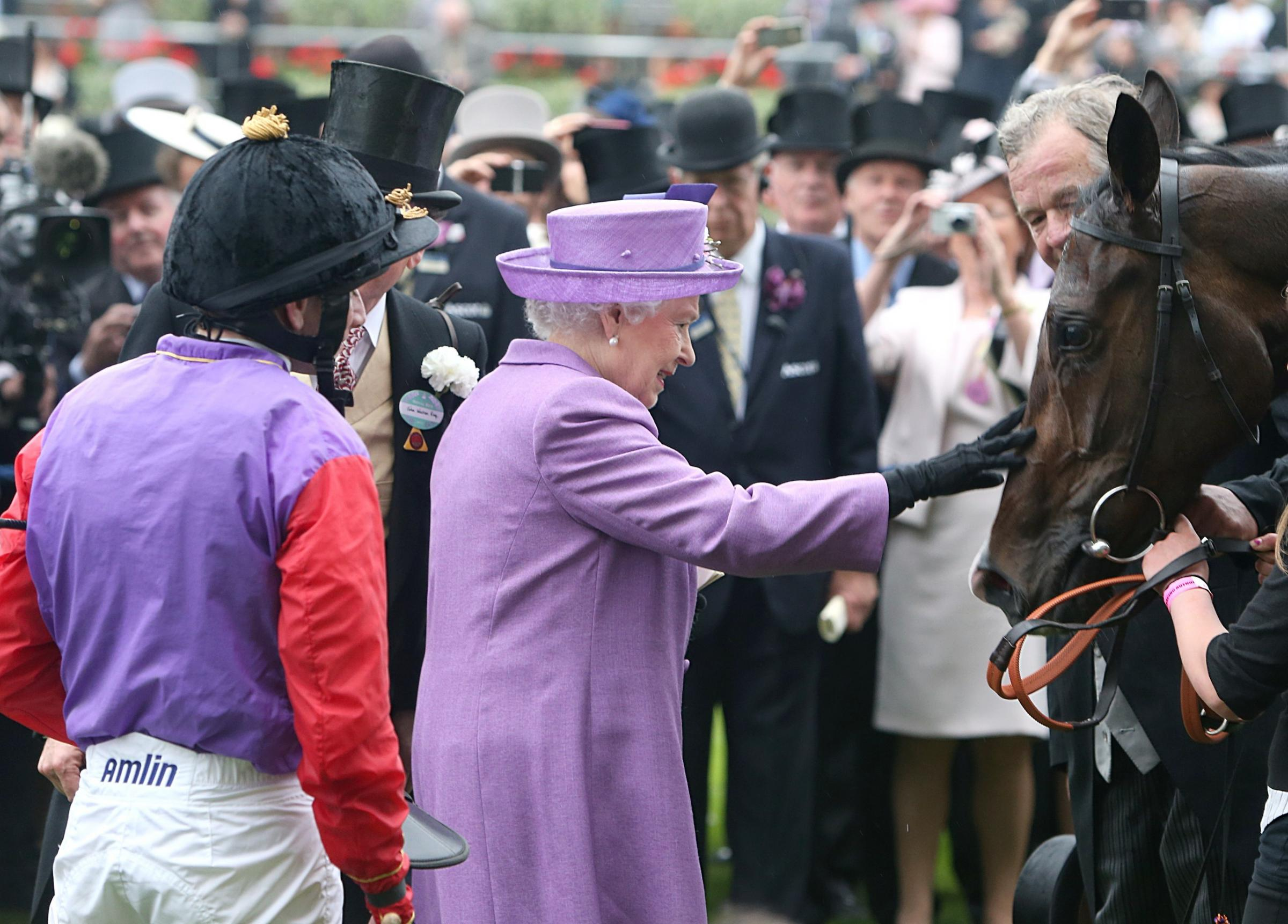 Queen Elizabeth II pats her horse Estimate after it won the 2