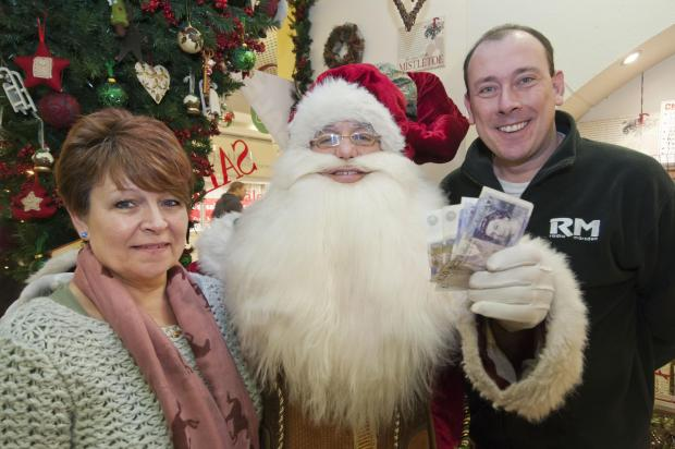 Father Christmas hands over the cash to Radio Marsden chairman Jason Reynolds and Yvonne Purdy-Mackey