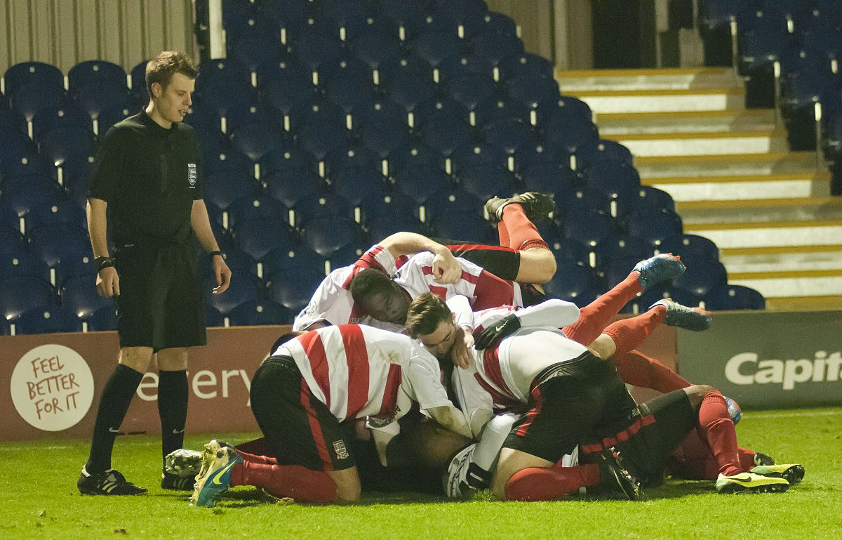 Hup hup: Daniel Sweeney is mobbed by his Kingstonian team-mates after bagging the winner against Dulwich Hamlet on Sunday          SP82218