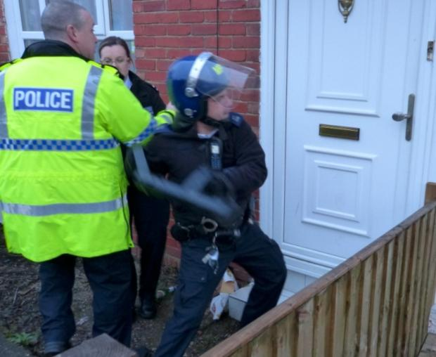 An officer uses a tool to smash open the door