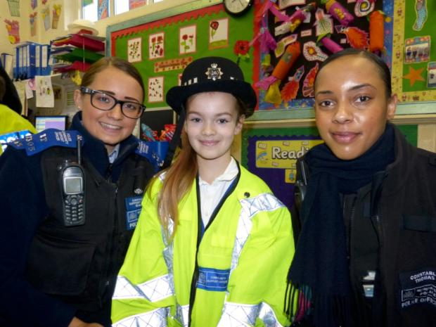 PCSO Sam English and PC Shola Thomas with a school pupil