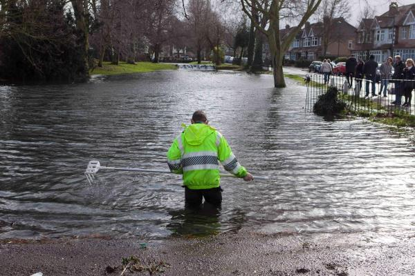 An Environment Agency worker tries to deal with flooding in Carshalton