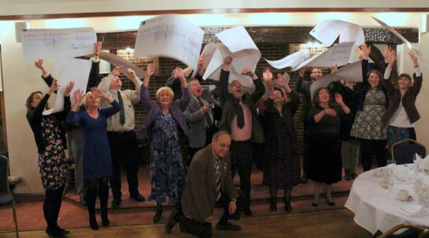 Charity representatives celebrate by throwing their giant cheques in the air