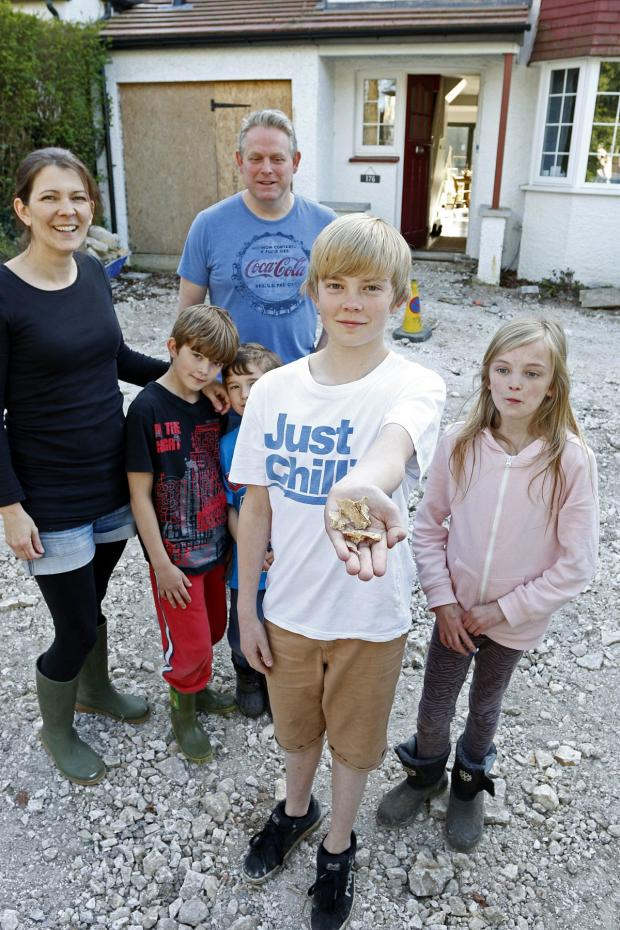 Sutton Guardian: The Carpenter family - mum and dad Alison and Michael and their children Jasmine, 11, Joel, 9, Toby, 7, and Zac, 13, holding bone fragments