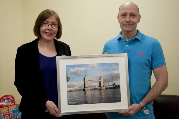 Mr Christian hands the new picture to St Helier's head of patient experience Shirley Edghill