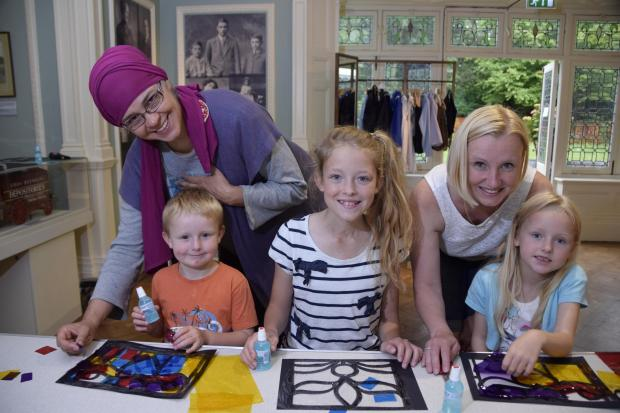 Crafty smiles: Families roll up their sleeves for some cutting and sticking