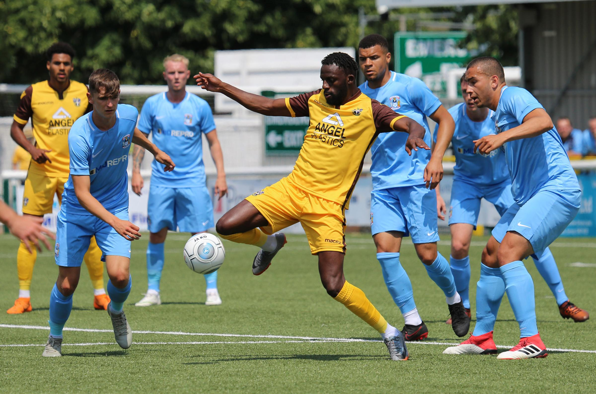 Sutton's Tom Bolarinwa, watched by new signing Jonah Ayunga (far left), shields the ball from a host of Coventry players including former United favourite Max Biamou. Picture: Paul Loughlin